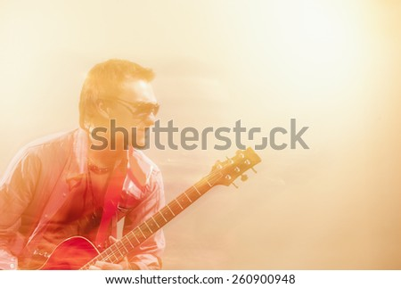 Expressive Guitarist Player With Acoustic Guitar. Shot with Combination of Strobes and Halogen Light to Create Mood and Atmosphere. Mixture of Flash and Halogen Lights.Horizontal Image Composition - stock photo
