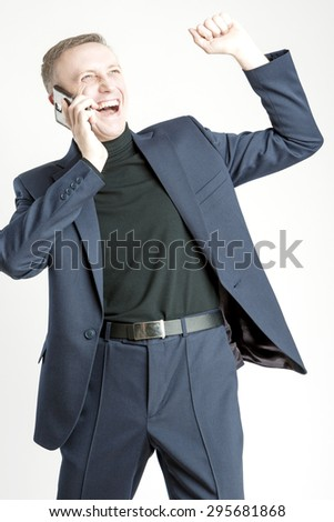 Expressive Handsome Caucasian Man In Elegant Suit Speaking by Cell Phone and Smiling. Against White, Vertical Image Composition - stock photo
