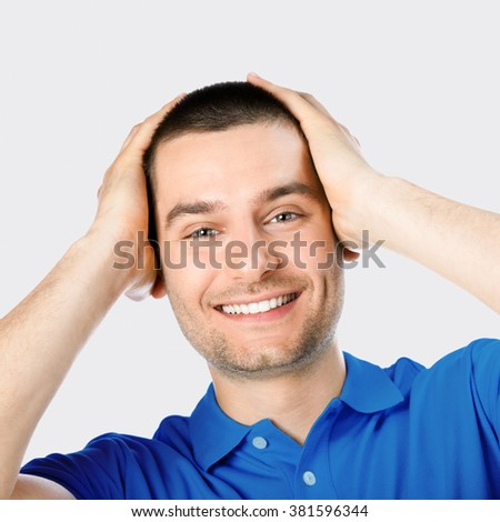 Expressive happy surprised man, against grey background - stock photo