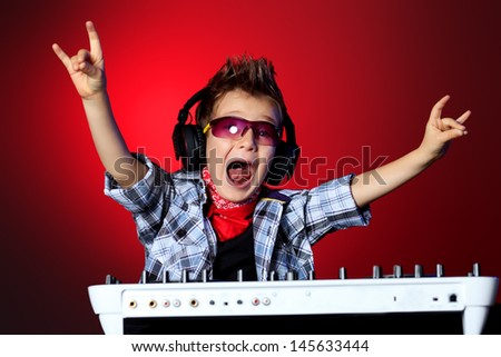 Expressive little boy DJ in headphones mixing up some party music. - stock photo