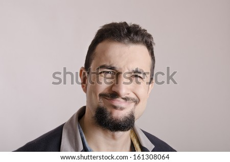 Expressive man with a goatee on studio background - stock photo