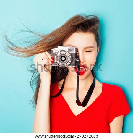 Expressive portrait of a beautiful brunette woman in a red dress in the studio on a blue background with a camera in his hands - stock photo