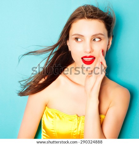 Expressive portrait of a beautiful young brunette woman in the studio on a blue background - stock photo