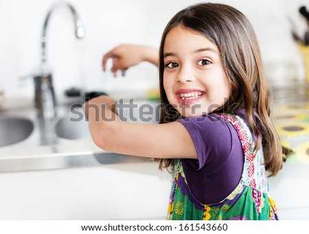 Expressive portrait of very cute girl washing hands - stock photo