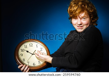 Expressive red-haired teenage boy showing time on big clock, business and time concept