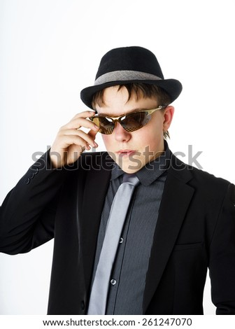Expressive teenage boy dressed in suit isolated on white background