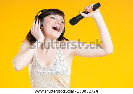 Expressive woman singing with a mike over yellow background - stock photo