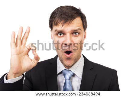 Expressive young businessman making  ok gesture over white background - stock photo