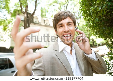 Expressive young businessman using an ear piece device and having a lively cell phone conversation while using his hands to gesture to the camera, smiling. - stock photo