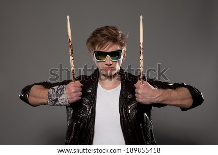 Expressive young drummer with drum stick  - stock photo