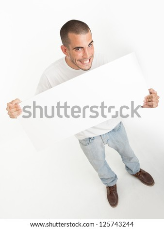 Expressive young man holding a blank board ideal for inserting your own message - stock photo