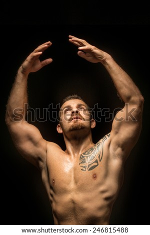 Expressive young man looking up with raides hands - stock photo