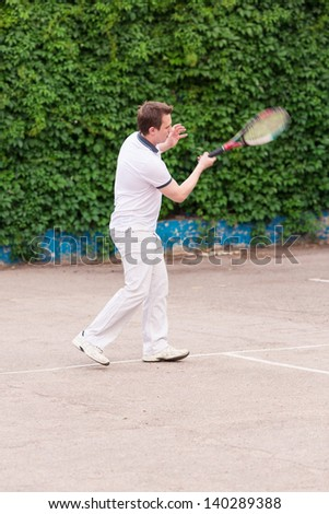 Expressive young man playing tennis outdoor - stock photo
