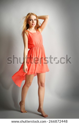 Expressive young model in orange dress on gray background