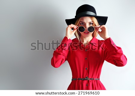 Expressive young model in red dress, black hat and sunglasses on gray background - stock photo