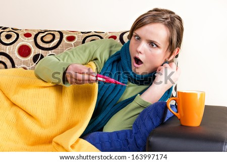 Expressive young woman having flu and checking thermometer at home - stock photo