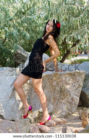 Expressive young woman in black dress outdoors
