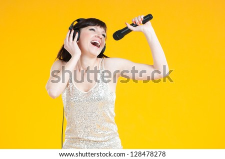 Expressive young woman in headphones holding mike and singing, yellow background - stock photo