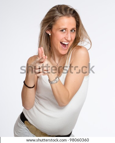 Expressive young woman with naughty expression pointing - stock photo