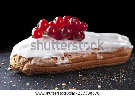 exquisite cream dessert eclair sprinkled with fresh redcurrant  - stock photo