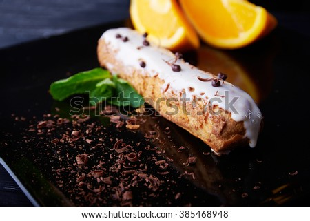 exquisite cream dessert eclair with fresh mint leaves  and orange slices on a mirror black plate and scattered chocolate.  Vertical shot. Shallow depth of field - stock photo