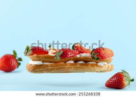 exquisite cream dessert eclair with fresh strawberry - stock photo