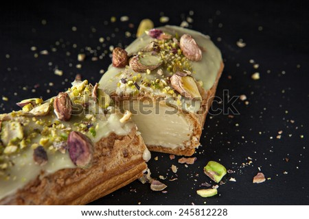 exquisite cream dessert eclair with pistachios with crumbs on the background