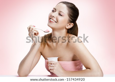 Exquisite woman with yogurt / studio photography of brown-eyed brunette girl holding spoon and a container of yogurt - isolated on background  - stock photo