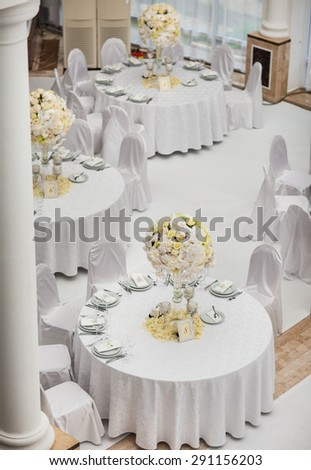 Exquisitely decorated wedding table setting with candles and bouquet of roses