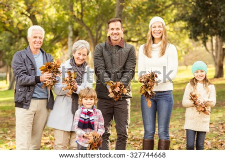 Extended family are ready to throw leaves around on an autumns day - stock photo