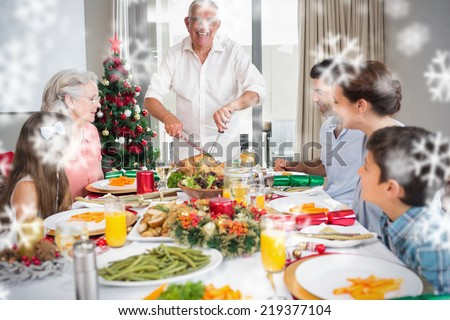 Extended family at dining table for christmas dinner in house against snowflakes