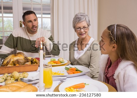Extended family at the christmas dinner table at home in the living room - stock photo