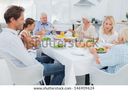 Extended family at the dinner table in kitchen - stock photo