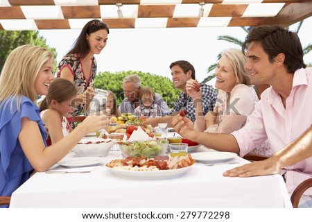 Extended Family Group Enjoying Outdoor Meal Together - stock photo