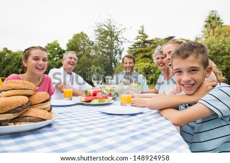 Extended family having dinner outdoors at picnic table smiling at camera - stock photo