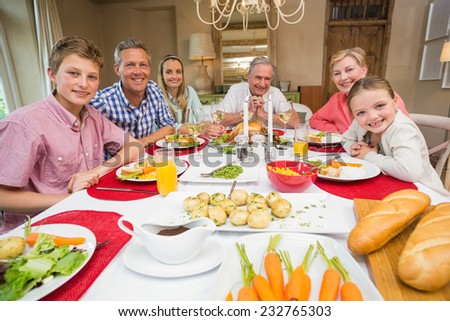 Extended family looking at camera at christmas time at home in the living room