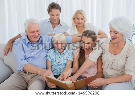 Extended family looking at their album photo in the living room - stock photo