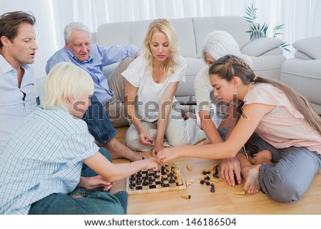 Extended family playing chess in the living room - stock photo