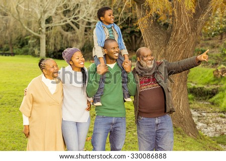 Extended family posing with warm clothes in parkland - stock photo