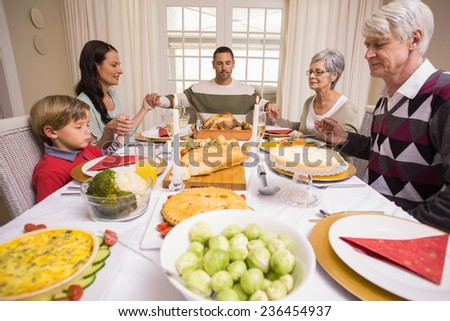 Extended family saying grace before christmas dinner at home in the living room