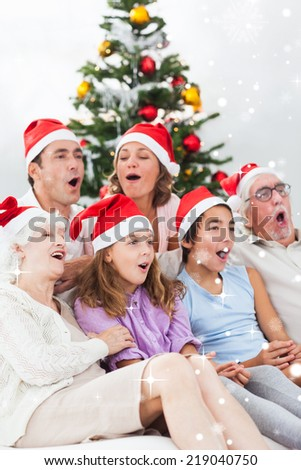Extended family singing christmas carols against snow falling - stock photo