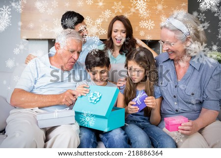 Extended family sitting on sofa with gift boxes in living room against snowflakes