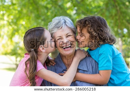 Extended family smiling and kissing in a park on a sunny day - stock photo