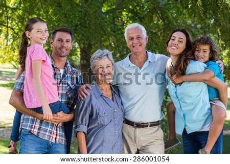 Extended family smiling at the camera on a sunny day - stock photo