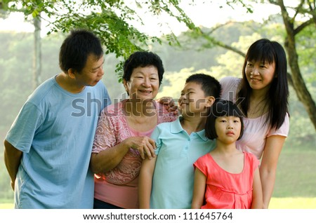 Extended family standing outdoors smiling - stock photo