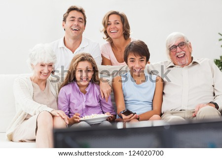 Extended family watching tv together on the couch - stock photo