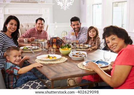 Extended Hispanic Family Enjoying Meal At Table - stock photo