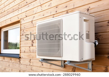 Exterior airconditioning unit on a wooden wall - stock photo