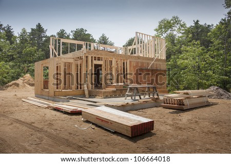 exterior framing of a new house under construction - stock photo