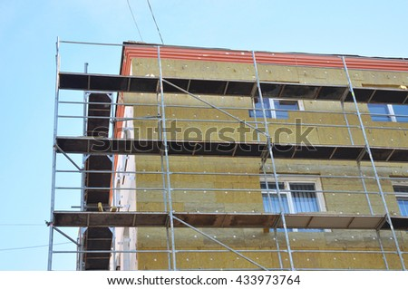 Exterior house wall heat insulation with mineral wool, building under construction. Insulation is defined as a material or combination of materials which retard the flow of heat.